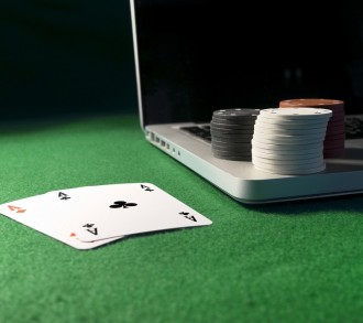 Laptop, poker cards and poker chips, on green background.