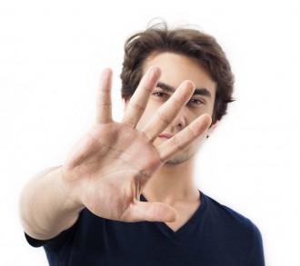 Portrait of young man gesturing stop