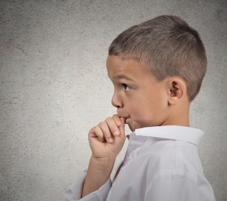 Closeup side view profile portrait, headshot boy with finger in mouth, sucking thumb, biting fingernail in deep thought isolated grey wall background. Negative emotions, facial expressions, feelings