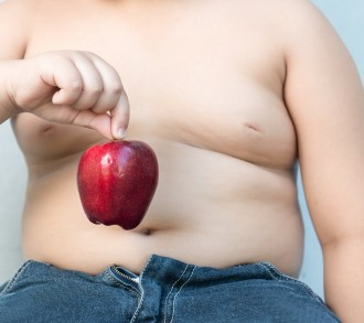Fat boy pick up red apple  on gray background
