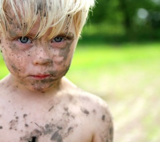 A sad looking little toddler boy is staring at the camera as he has gotten into trouble playing in the dirt and mud outside on a summer day.